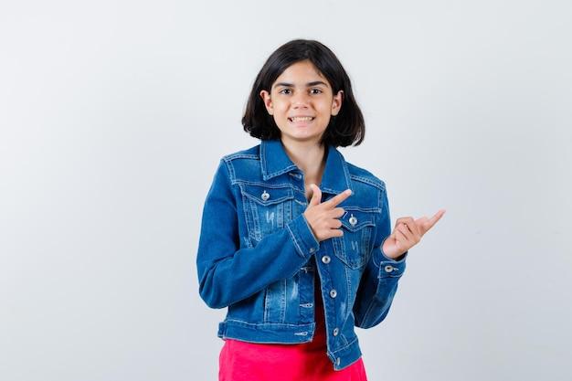Jong meisje wijst naar rechts met wijsvingers in rood t-shirt en spijkerjasje en ziet er gelukkig uit. vooraanzicht.