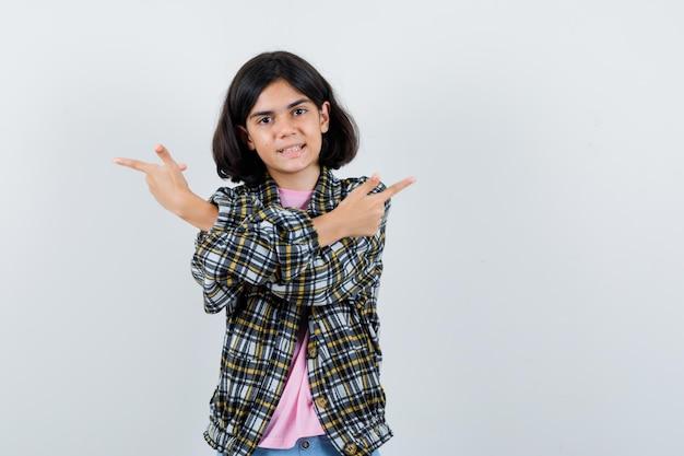 Jong meisje wijst naar tegenovergestelde richtingen in geruit overhemd en roze t-shirt en ziet er schattig uit. vooraanzicht.