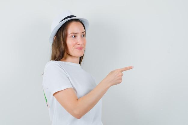 Jong meisje wijst opzij in wit t-shirt, hoed en ziet er schattig uit. vooraanzicht.
