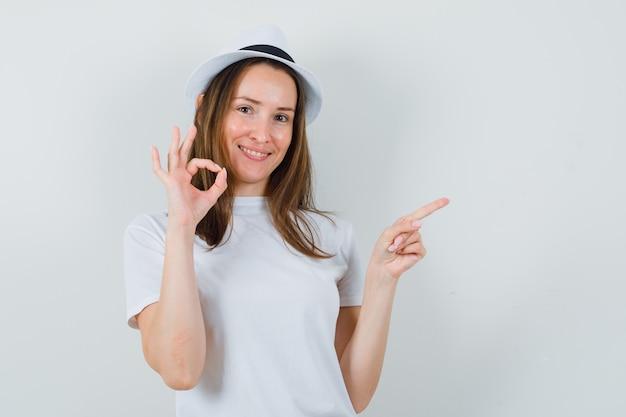 Jong meisje wijst opzij, toont ok gebaar in wit t-shirt, hoed en kijkt gelukkig, vooraanzicht.