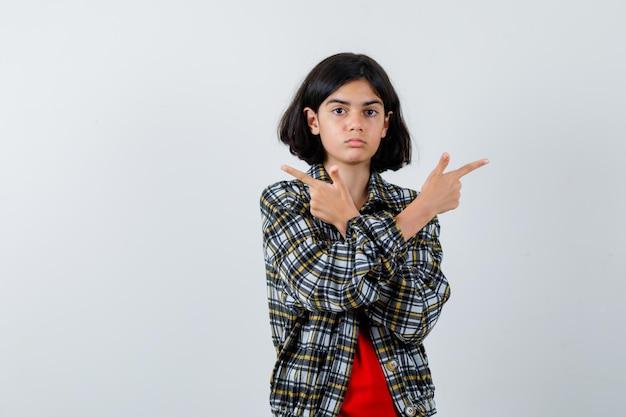 Jong meisje wijst tegengestelde richtingen in geruit overhemd en rood t-shirt en kijkt serieus. vooraanzicht.