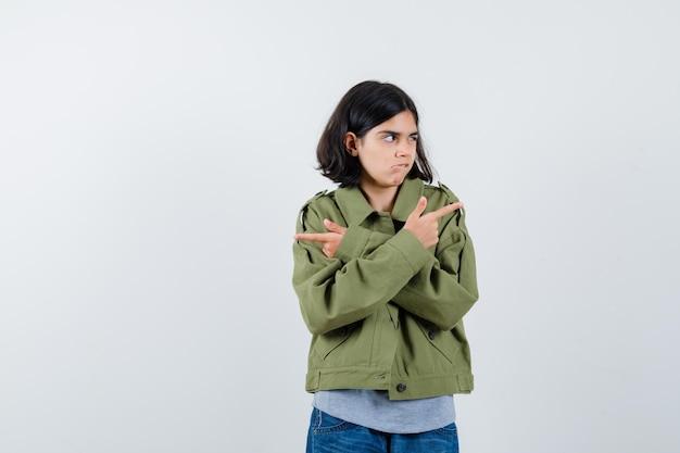 Jong meisje wijst tegengestelde richtingen in grijze trui, kaki jas, jeansbroek en ziet er serieus uit. vooraanzicht.