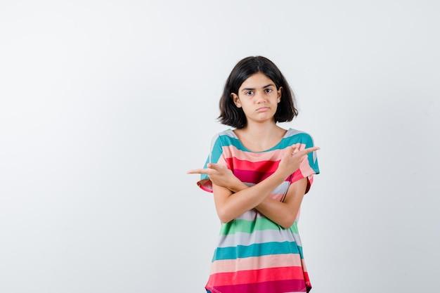Jong meisje wijst tegenovergestelde richtingen met wijsvingers in kleurrijk gestreept t-shirt en ziet er schattig uit, vooraanzicht.