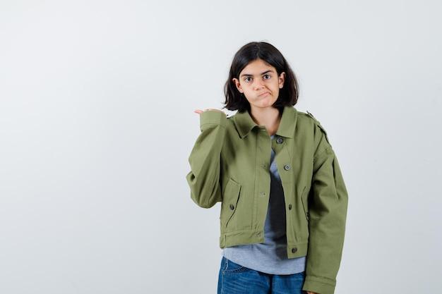 Jong meisje wijst weg, gebogen lippen in grijze trui, kaki jas, jeansbroek en ziet er schattig uit, vooraanzicht.