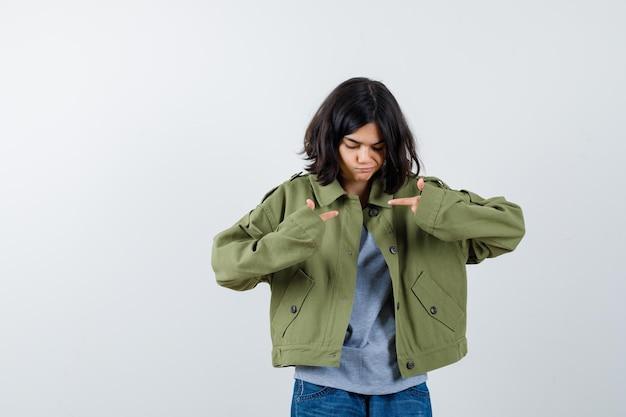 Jong meisje wijst zichzelf in grijze trui, kaki jas, jeansbroek en kijkt gefocust, vooraanzicht.