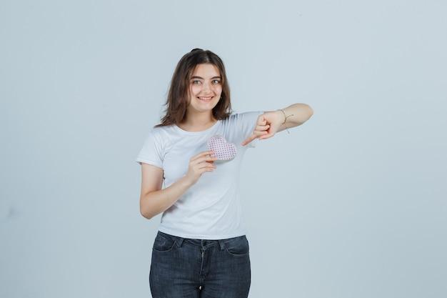 Jong meisje wijzend geschenkdoos terwijl het in t-shirt, spijkerbroek en op zoek vrolijk, vooraanzicht.