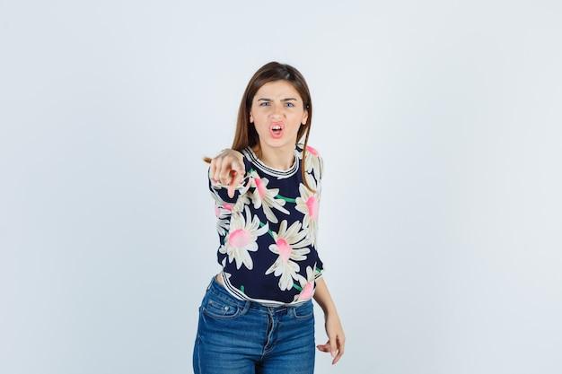 Jong meisje wijzend op camera met wijsvinger in bloementrui, jeans en geagiteerd kijken. vooraanzicht.
