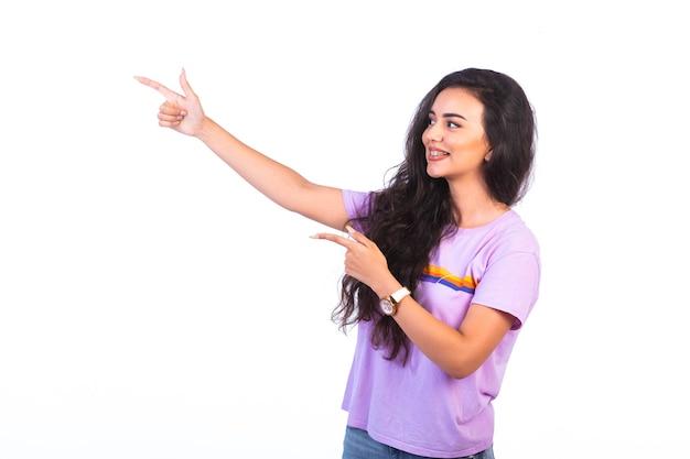 Jong meisje wijzend op iets en presentatie maken op wit oppervlak