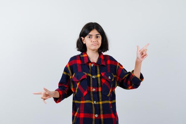 Jong meisje wijzend op tegengestelde richtingen in geruit overhemd en ziet er schattig uit, vooraanzicht.
