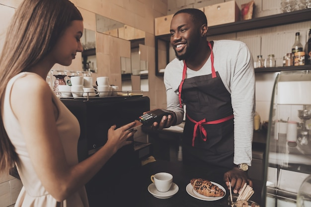 Jong meisje wordt het café berekend met een creditcard