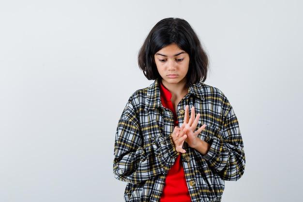 Jong meisje wrijft over de handen, kijkt naar beneden in geruit overhemd en rood t-shirt en ziet er serieus uit, vooraanzicht.