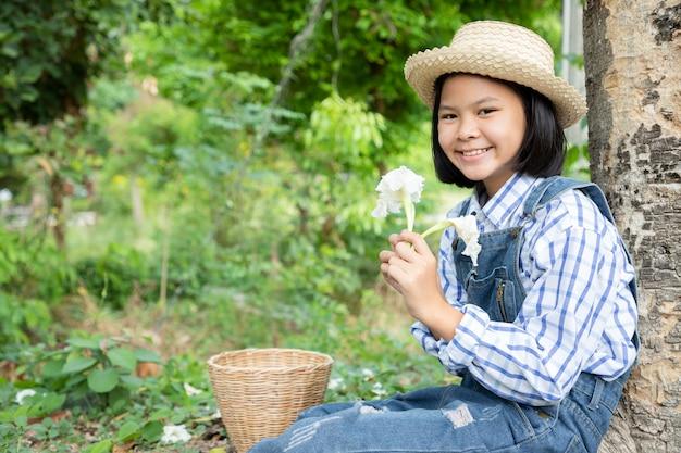Jong meisje zat onder een grote boom en haar hand hield witte bloemen na de oogst. dolichandrone serrulata wordt geclassificeerd als wilde groenten en kruiden, maar ook als sier- en heilige planten. kopieer ruimte
