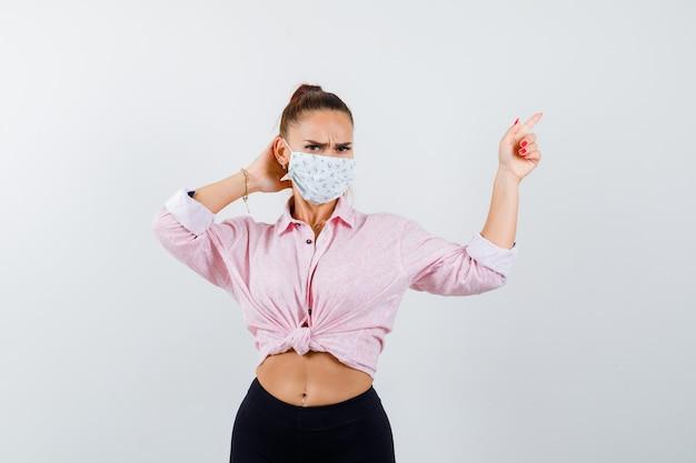Jong meisje zet een hand achter het hoofd, wijst naar rechts met wijsvinger in roze blouse, zwarte broek, masker en kijkt serieus, vooraanzicht.
