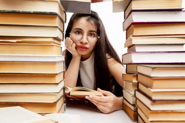 Jong meisje zit aan een tafel met een stapel boeken. triest brunette met een bril. training en onderwijs. detailopname.