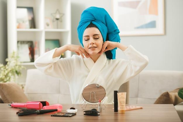 Jong meisje zit aan tafel met make-up tools in de woonkamer