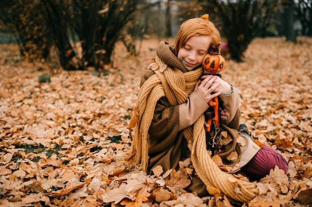 Jong meisje zit in het najaar park met speelgoed