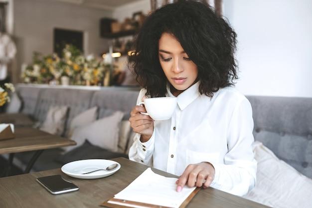 Jong meisje zit in restaurant met kopje koffie in de hand en zorgvuldig