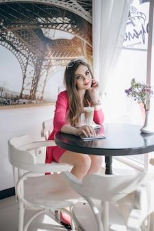 Jong meisje zitten in een restaurant met een smoothie