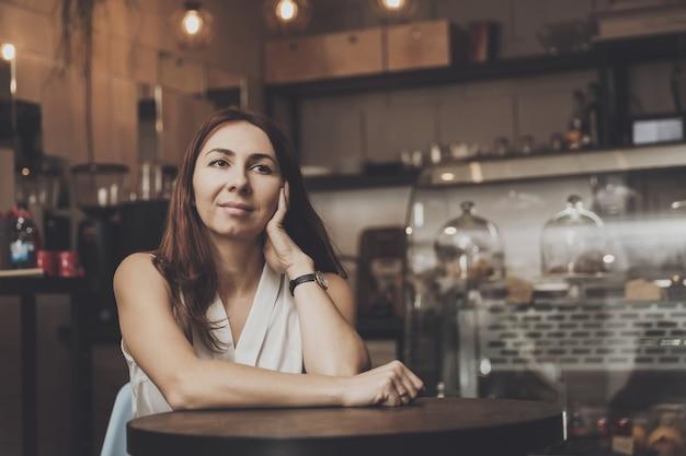 Jong meisje, zittend in een café in afwachting van een jonge man