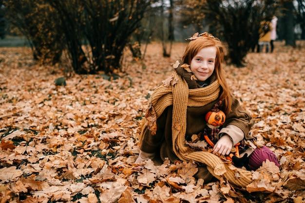 Jong meisje, zittend in het najaar park