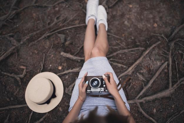 Jong meisje, zittend op de grond met een vintage camera