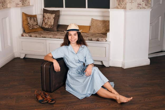 Jong meisje zittend op de vloer met een koffer.