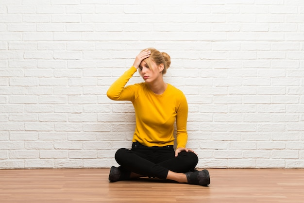 Jong meisje, zittend op de vloer met verrassing en geschokt gelaatsuitdrukking