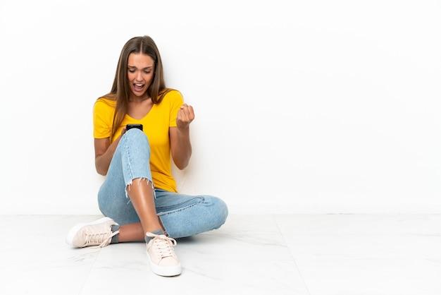 Jong meisje, zittend op de vloer verrast en een bericht verzenden
