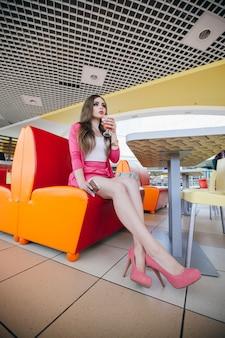 Jong meisje zittend op een oranje bank in een restaurant het drinken van een drankje