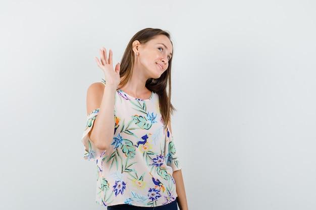 Jong meisje zwaaiende hand om afscheid te nemen in shirt, spijkerbroek en op zoek blij, vooraanzicht.