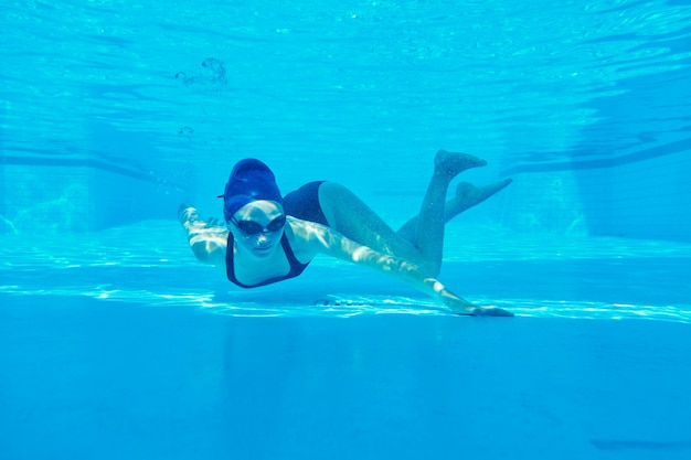 Jong meisje zwemmer in zwembroek met bril en badmuts onderwater in zwembad