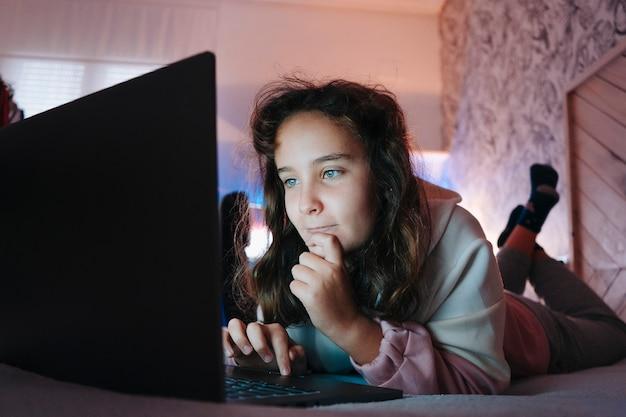 Jong meisjesjong geitje dat op haar bed legt dat iets op internet zoekt. video-oproep.