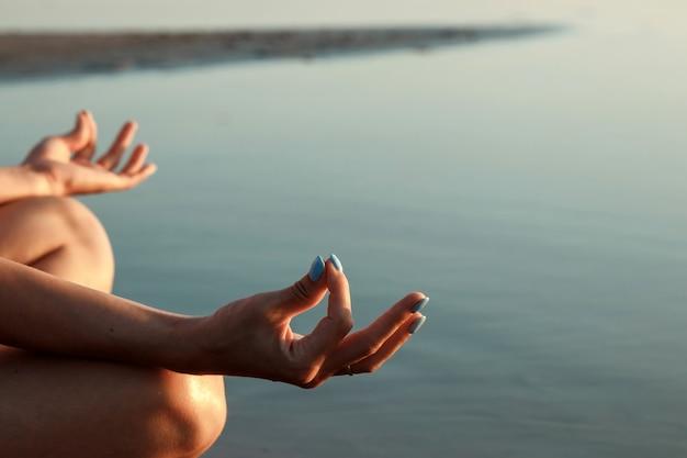 Jong meisjessilhouet, yoga op aard, op een van een meer en mooie zonsondergang