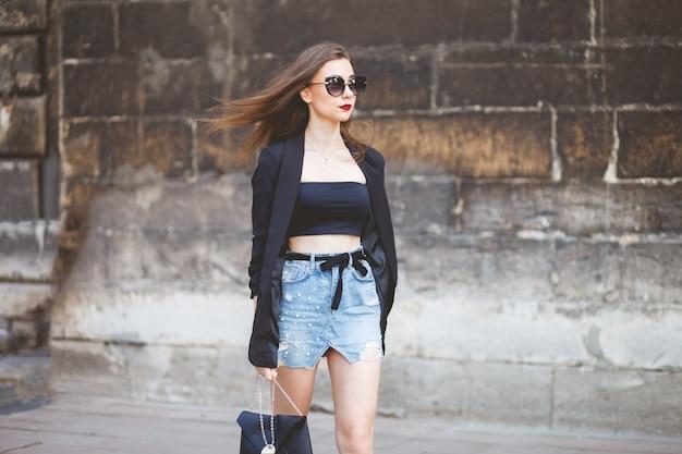 Jong model dat langs de straat tegen een steenmuur loopt