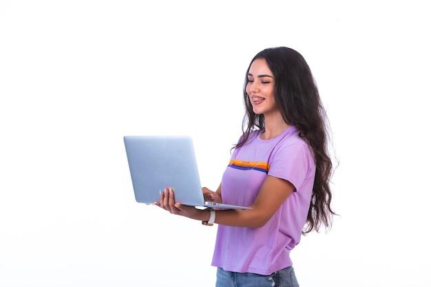 Jong model dat zilveren laptop houdt en videogesprek heeft.