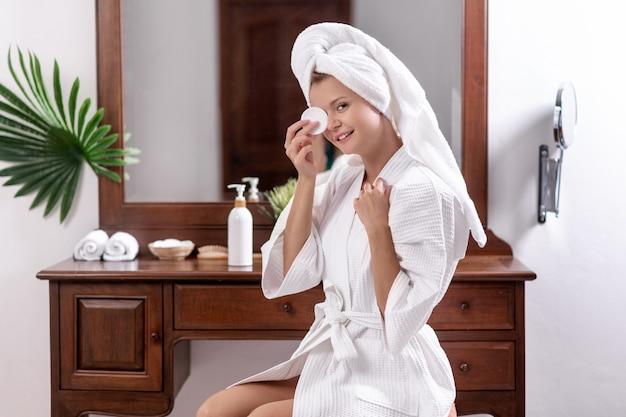 Jong model in een badjas en een handdoek op haar hoofd zittend op een stoel in de buurt van de tafel