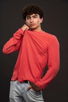 Jong model in het rode overhemd stellen door handen op zijn hals te leggen.