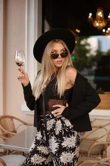 Jong model meisje in modieuze zomer outfit wijn drinken in een cafe op de stad straat.
