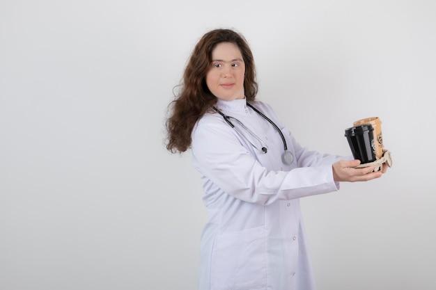 Jong model meisje in wit uniform met een karton met kopjes koffie.