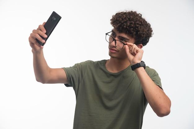 Jong model met krullende haren die zijn foto nemen en een bril dragen.