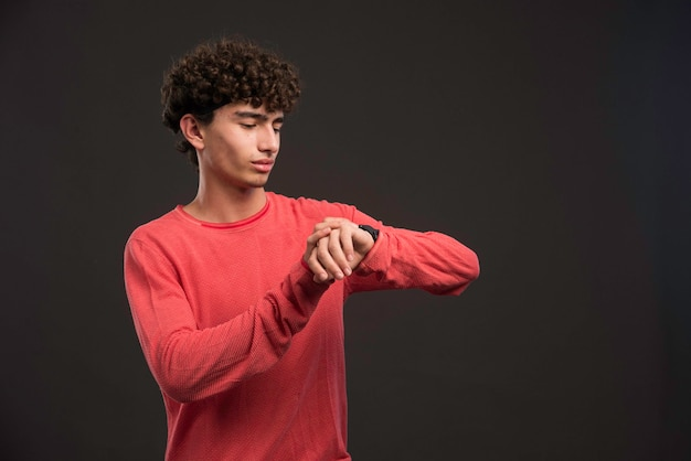 Jong model met krullende haren die zijn tijd controleren.
