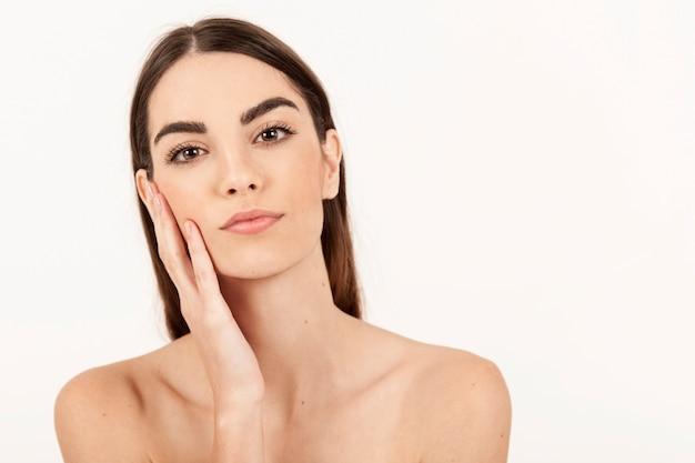 Jong model poseren met een hand op haar gezicht