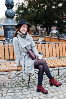Jong modelmeisje in een grijze laag en zwarte hoed met leerhandtas op schouders die op bank zitten