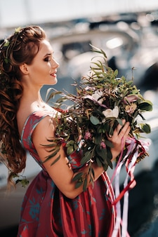 Jong modelmeisje in een mooie jurk met een boeket bloemen op het strand in frankrijk. meisje met bloemen in het voorjaar van de provence aan de franse rivièra.