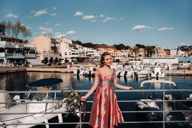 Jong modelmeisje in een mooie jurk met een boeket bloemen op het strand in frankrijk