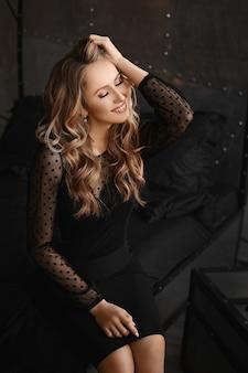 Jong modelmeisje met avondmake-up in een zwarte cocktailjurk glimlachend en poseren met gesloten ogen binnenshuis