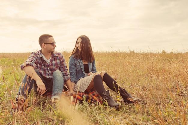 Jong modern modieus paar in openlucht. romantisch jong koppel verliefd buiten op het platteland