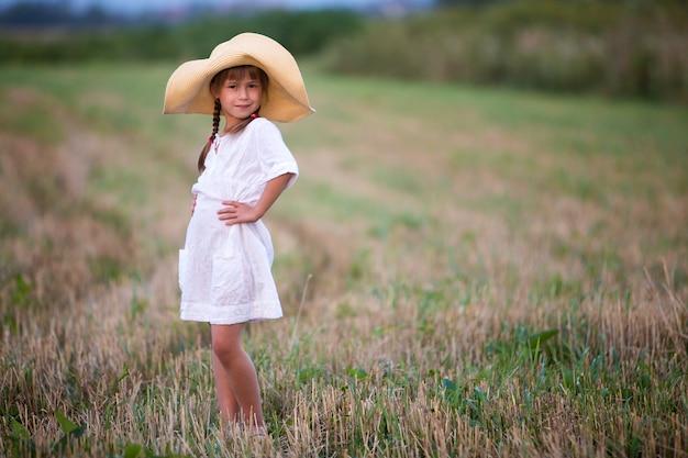 Jong modieus mooi schattig meisje met lange vlechten in mooie witte zomerjurk en grote strohoed.