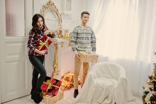 Jong modieus paar met kerstmisgiften en nieuwjaardecoratie