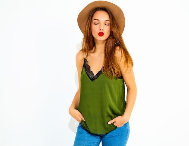 Jong modieus vrouwenmodel in toevallige de zomer groene kleren en bruine hoed met rode lippen, die dichtbij witte muur stellen